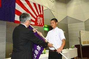 記念大会の助成金などで作られた校旗を受け取る鳥取東の山根弘志主将=米子市文化ホール